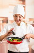Woman chef holding red skillet with chopped vegetables inside, adding salt from Stock Photos