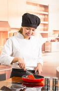 Woman chef wearing full cooking outfit standing frying vegetables in red skillet Stock Photos
