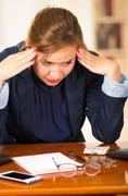 Business woman sitting by desk, elbows on table and head bent over as expressing - stock photo