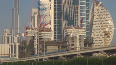 Metro train pass suspended railway in Dubai crowded town construction site crane Stock Footage