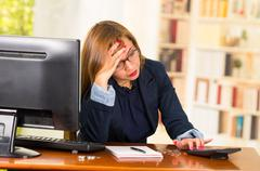 Business woman wearing glasses sitting by desk with computer expressing mild Stock Photos