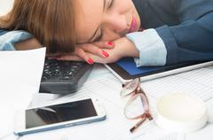 Office woman bent over white desk resting or sleeping with computer keyboard - stock photo