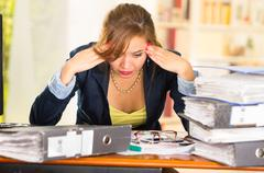 Business woman sitting by desk, paper files spread out, elbows on table and head Stock Photos