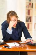 Business woman sitting by desk with frustrated and tired body language, touching Stock Photos