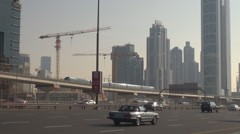 Pan left of metro train transportation in Dubai heavy traffic car on busy avenue Stock Footage