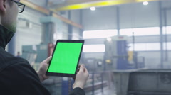 Footage of a tablet with green mock-up screen in industrial environment Stock Footage