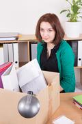 Sad businesswoman carrying box with her belongings in office Stock Photos