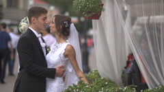 Bride and groom hugging on the street, the bride holding a bouquet - stock footage