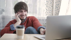 Happy Young Man Freelancer Working with Modern Laptop and Phone in Cafe taking Stock Footage