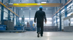 Factory worker in a hard hat is walking through industrial facilities Stock Footage