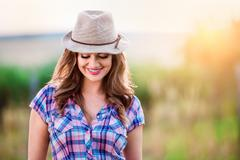 Gardener in checked shirt and hat, green sunny nature - stock photo