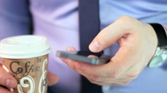 Close-up man's hands using mobile phone touchscreen and cofee Stock Footage