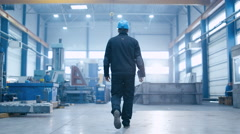 Follow footage of factory worker that is walking through industrial space - stock footage