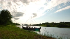 Replica of old Viking longship stand at grassy river shore. bright clouds on sky Stock Footage
