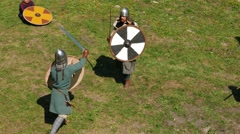 Northman warriors fight on grass arena, duel battle using sword and round shield - stock footage