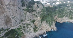 CINEMATIC TILT SHOT FLY OVER OF PEOPLE ON CAPRI COASTLINE TO BEAUTIFUL CITY Stock Footage