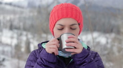 Beautiful young woman pouring and drinking tea from a thermos cup outdoors HD Stock Footage