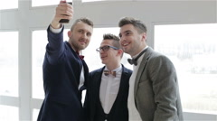 Three representative men in suits and bow ties making selfie near the window - stock footage