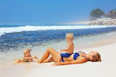 Happy family - mother, baby son, daughter sunbathing on sea beach Stock Photos