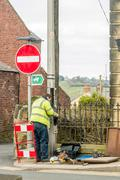 Workman fixing telephone line on a Welsh street. - stock photo