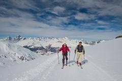 Two elderly men practice ski mountaineering Stock Photos