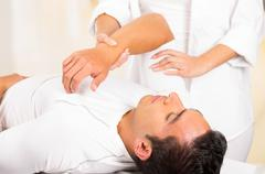 Male patient lying down with female physio therapist hands performing some Stock Photos