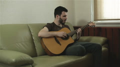 A handsome young man singing and playing the guitar Stock Footage