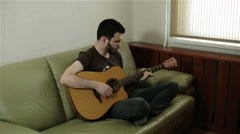 A man with a beard sitting cross-legged playing the guitar - stock footage