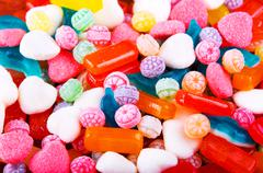 Closeup variation of colorful hard candy lying mixed as seen from above Stock Photos