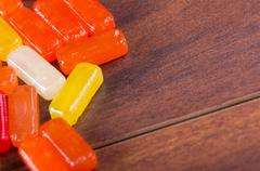 Closeup colorful rectangular hard candy lying on wooden surface - stock photo