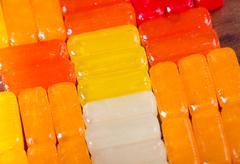 Closeup rectangular colorful shiny hard candy lined up - stock photo