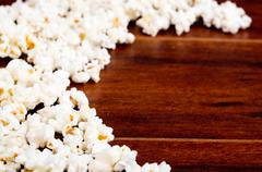 Closeup pile of white fluffy popcorn lying mixed together on wooden surface Stock Photos