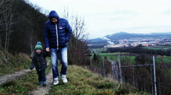 Father and little son are walking along a mountain path. - stock footage