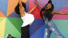 Women jumping on colorful wall Stock Footage