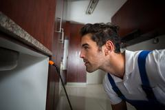 Manual worker concentration below sink - stock photo