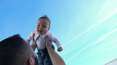 Young father playing with his small, funny son against the sky, super slow motio Stock Footage