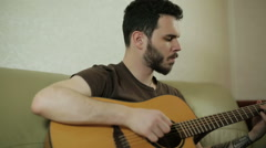 A young guy playing the guitar - stock footage