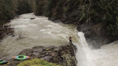 Peering from the edge, an adventurous whitewater kayaker scouts a rapid stream  - stock footage