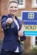 Female Realtor Standing Outside Residential Property Holding Keys - stock photo