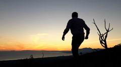 Young man climbing on the hills, and enjoy sunset, super slow motion Stock Footage