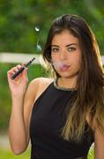 Classy brunette lady wearing black dress standing in garden environment smoking - stock photo