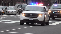 Police cruiser accompanies VIP van through intersection Stock Footage