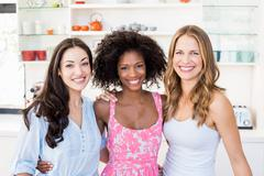 Portrait of beautiful women standing with arm around in kitchen - stock photo