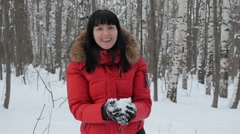 Woman wearing a red jacket throwing snow in the air in winter holidays Stock Footage