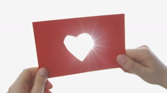 Girl holding up a Sheet of Paper from which she has cut out a Heart Shape - stock footage