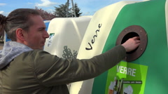 Young man throwing glass gabage in a recycling container, France - with sound Stock Footage