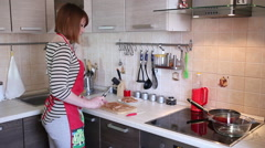 Young woman is cooking in the kitchen Stock Footage