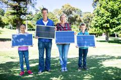 Family holding a solar panel - stock photo