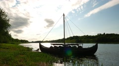 Dark Karvi boat silhouette at bright back light, grass shore of river Stock Footage