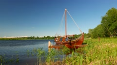 Traditional Viking boat stand at grassy river shore, calm sunny evening Stock Footage